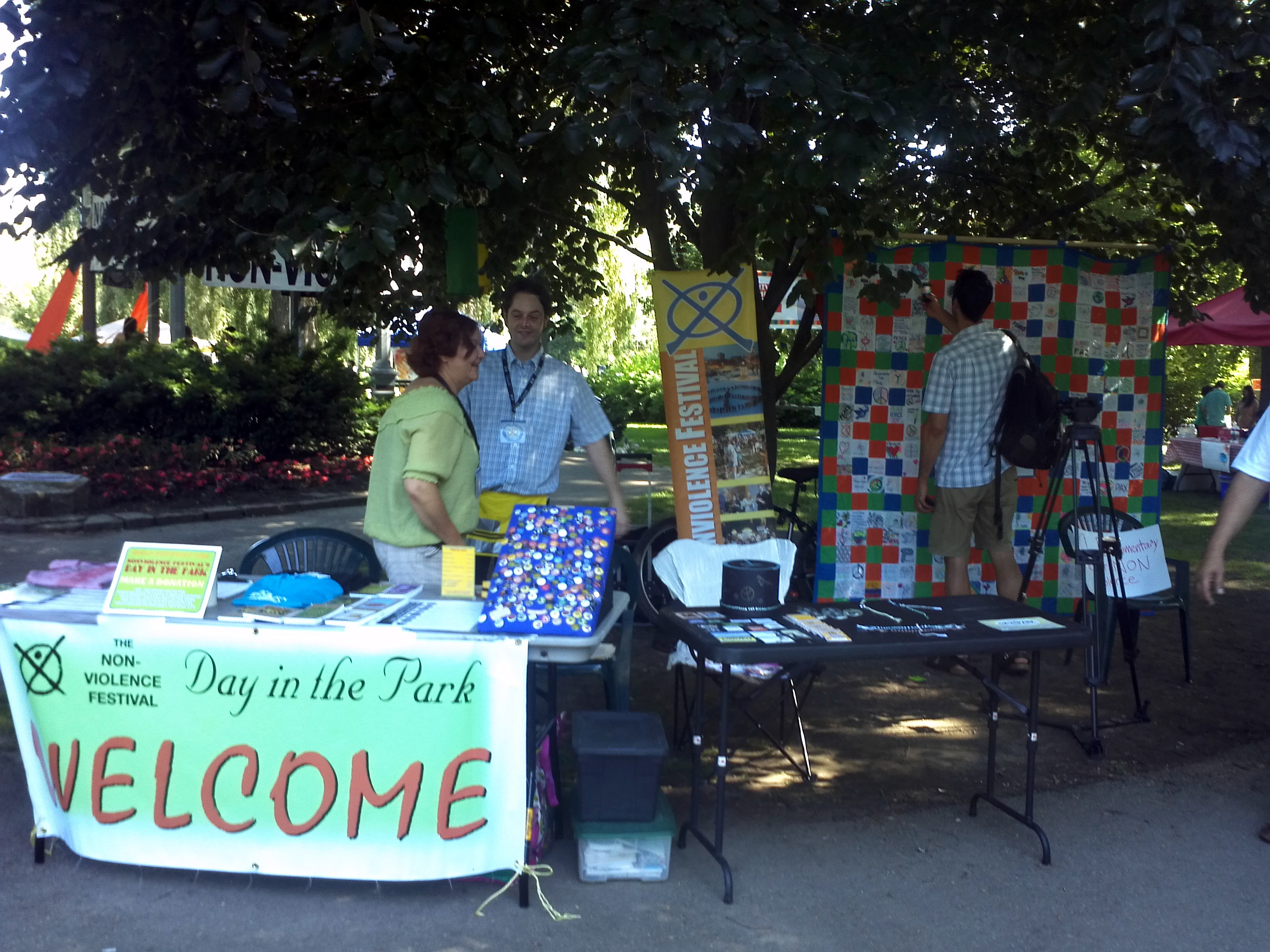 "The Welcome booth, showing banner ""The Non-Violence Festival Day in the Park WELCOME"""
