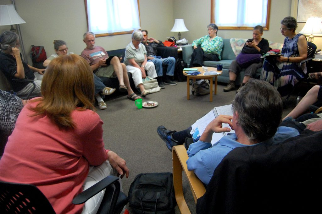 People sitting around the room at the KWPeace Potluck Meeting for Summer 2018