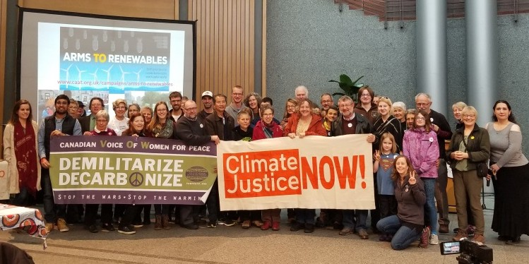 """People holding banners """"Demilitarize Decarbonize"""" and """"Climate Justice Now!"""""""
