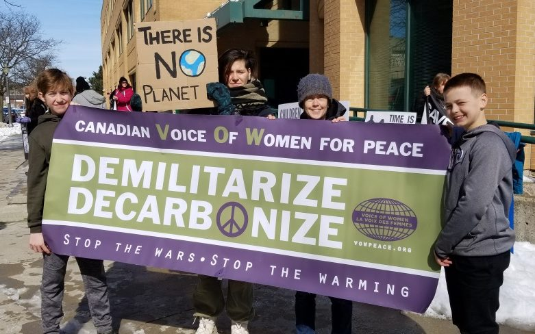 Sophia Kudriavtsev, Tamara Lorincz, and two kids hold a banner: Canadian Voice Of Women for Peace | Demilitarize | Decarbonize | Stop The Wars - Stop The Warming