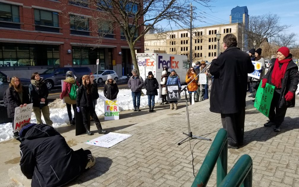 Bob Jonkman at the microphone speaking to a crowd of students with posters